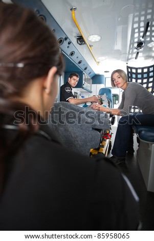 Ambulance employee and caregiver looking at camera while senior woman receives care - stock photo