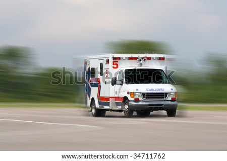 ambulance in motion driving down road - stock photo