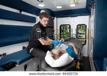 Ambulance interior with male paramedic measuring pulse on senior woman - stock photo