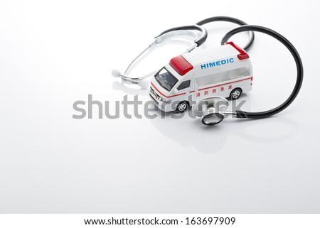 Ambulance miniature car and Stethoscope on white background - stock photo