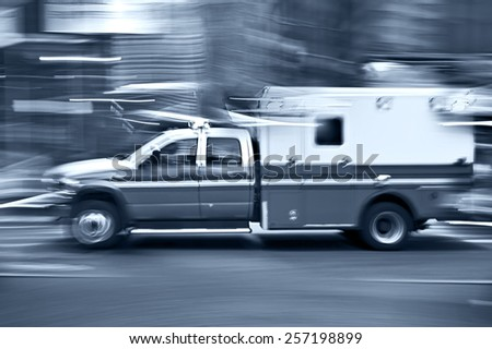 ambulance on emergency call in motion blur and blue tonality - stock photo