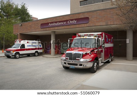 Ambulance pulling up to emergency entrance of a hospital - stock photo