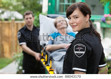 Ambulance worker portrait with stretcher, paitient and co-worker - stock photo