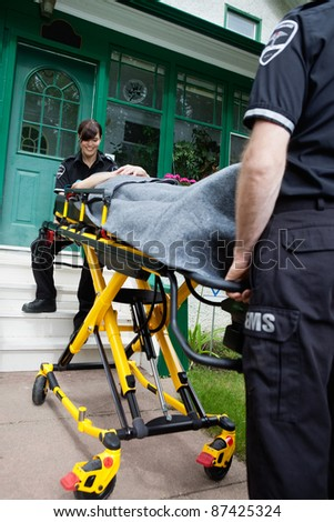 Ambulance worker smiling to patient outside house - stock photo