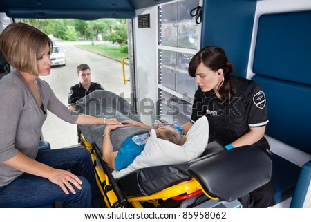 Ambulance workers caring for a senior woman with young caregiver at side - stock photo