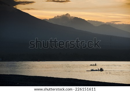 Amed, Bali. At sunrise a fishing boat, called a jukung, returns to shore after a night fishing for mackerel. The volcano, Mt. Agung, is in the background. - stock photo