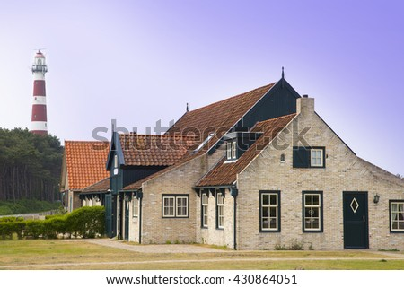 Ameland, The Netherlands - May 21, 2016: Typical old farmer house on the island Ameland, The Netherlands with famous lighthouse. - stock photo