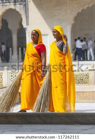 AMER, INDIA - NOV.19: Unidentified women of fourt class in brightly colored sari clean the Amber palace on November 19,2012 in Amer,India. They earn 300 IRP for two hours paid by the government. - stock photo