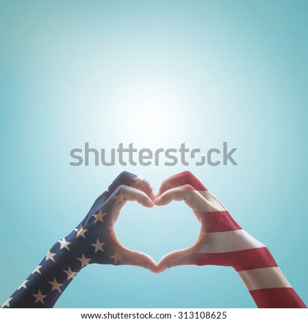 America flag pattern on people hands in heart shaped against blue sky background: United states of america: Columbus day, Remembering patriot day/ Independence day/ constitution and citizenship day  - stock photo