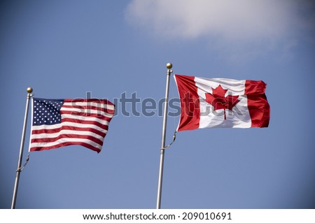 American and Canadian flags fly side by side - stock photo