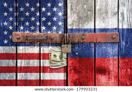 American and Russian flag and dollars with padlock doors - stock photo