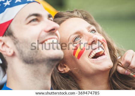 American and Spanish fans Couple at Stadium - stock photo