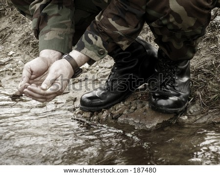 American army soldier washing in stream