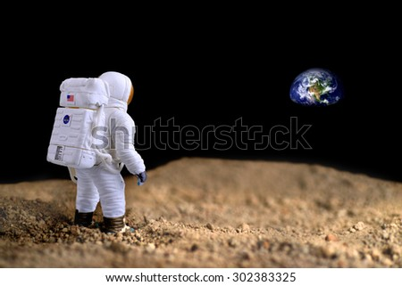 American Astronaut on the moon looking at earth on the background, elements of this image furnished by NASA.