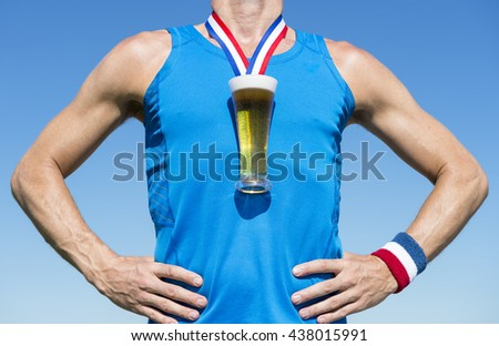 American athlete standing with first place gold medal in the shape of a glass of beer standing in front of blue sky - stock photo