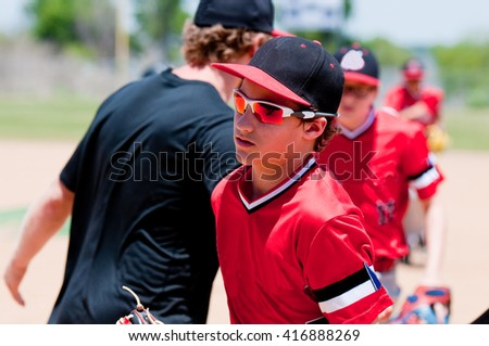 American baseball game with player running off field and coach in background. - stock photo