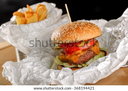 American big beef burger with cheddar cheese, pickles, salad, tomatoes and fried potatoes - stock photo