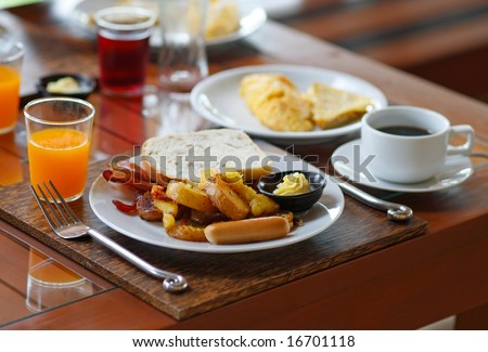 American Breakfast set with omelet, bacon, sausages, bread, potatoes, orange juice and a cup of coffee