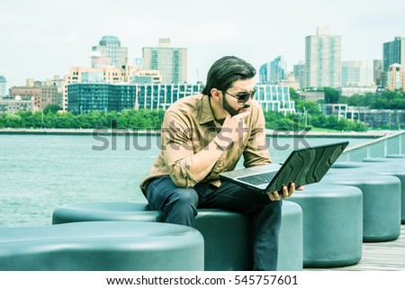 American Business Man traveling, working in New York, wearing brown shirt, sunglasses, sitting by river, hand touching chin, reading laptop computer. Brooklyn on background. Color filtered effect
