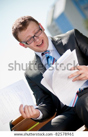 american businessman sitting on a park bench working on his document