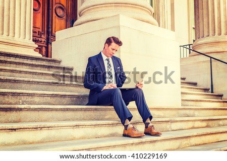 American Businessman traveling, working in New York, dressing in black suit, necktie, white undershirt, yellow leather shoes, sitting on stairs outside vintage office, working on laptop computer. - stock photo