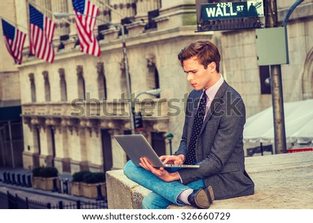 American businessman traveling, working in New York. Young blonde, handsome student, wearing blazer, necktie, jeans, crossing legs, reading, working on laptop computer. Wall Street sign on background. - stock photo