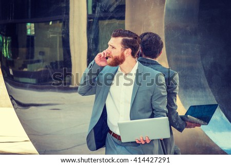 American Businessman with beard, mustache working in New York, wearing cadet blue suit, standing against metal mirror wall, working on laptop computer, talking on cell phone. Instagram filtered effect - stock photo