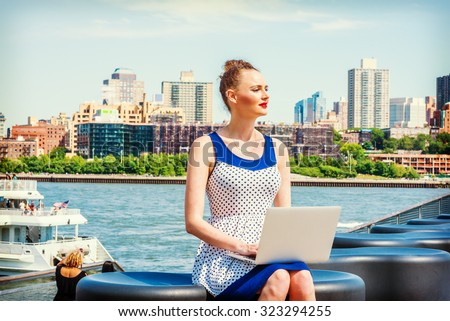 American businesswoman traveling, working in New York. Wearing blue, white polkadot dress, a young sexy lady sitting on bench at harbor, working on laptop computer, reading, thinking. Instagram effect - stock photo