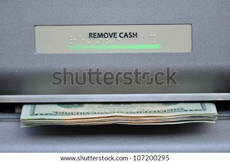 American cash being dispensed from a bank automated teller machine, or ATM - stock photo