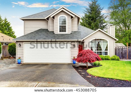 American classic home with beige exterior paint. Beautiful curb appeal. - stock photo