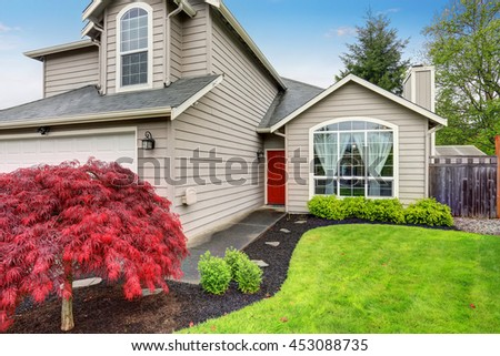 American classic home with beige exterior paint, concrete walkway and green lawn. - stock photo