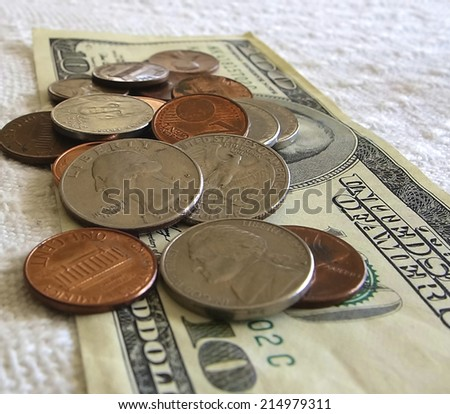 American Coins on a bed of Dollars - stock photo