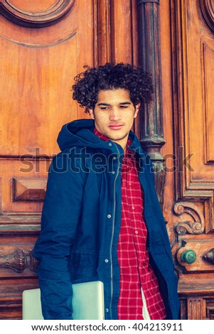 American college student studying in New York. Wearing blue jacket with hood, a guy with freckle face, curly long hair, holding laptop computer, standing by classroom doorway, looking down, thinking. - stock photo