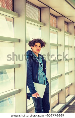 American college student studying in New York. Wearing blue jacket with hood, a guy with freckle face, curly long hair, holding laptop computer, standing on walkway, against glass wall on campus.  - stock photo