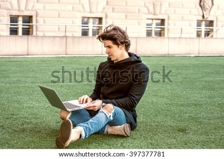 American college student studying in New York, wearing fashionable long coat with hood, jeans, boots, crossing legs, sitting on green lawn on campus, working on laptop computer. Color filtered effect. - stock photo