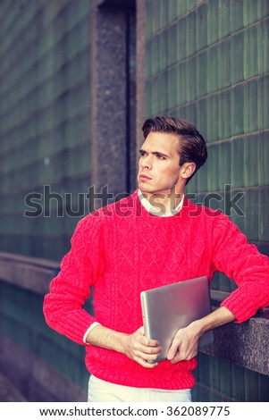 American college student studying in New York, wearing red knit sweater, holding laptop computer, standing against green wall on campus, confidently looking forward, Instagram filtered effect.  - stock photo