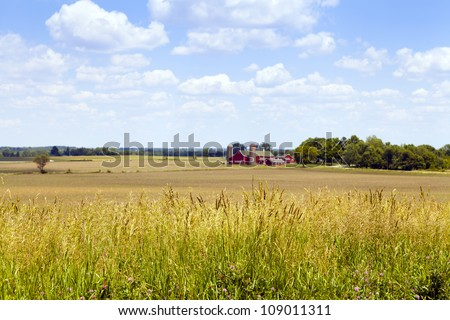 American Countryside With Red Farm in the Background and Highway - stock photo