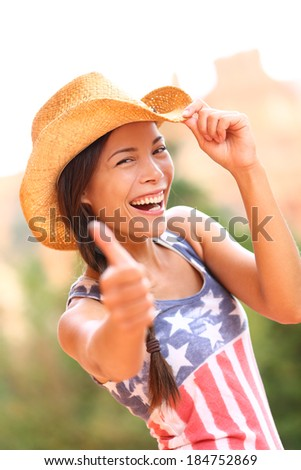 American cowgirl woman happy excited giving thumbs up wearing cowboy hat outdoors in countryside. Cheerful elated joyful woman smiling enjoying freedom. Beautiful multiracial Asian Caucasian female. - stock photo