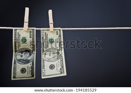 American currency. USA money, Dollar bills hanging on rope attached with clothes pins. - stock photo