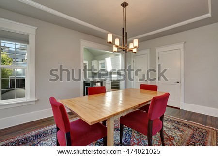 American dining room interior with table and red chairs on colorful rug, modern chandelier above the table. Northwest, USA
