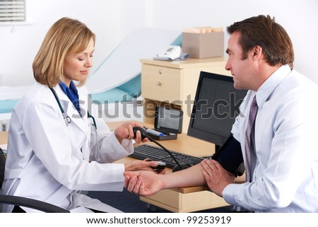 American doctor taking patient's blood pressure - stock photo