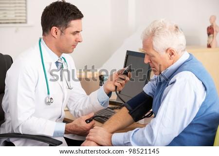 American doctor taking senior man's blood pressure - stock photo