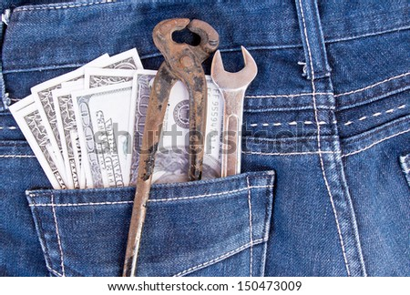 American dollar bills and tools in jeans pocket background - stock photo