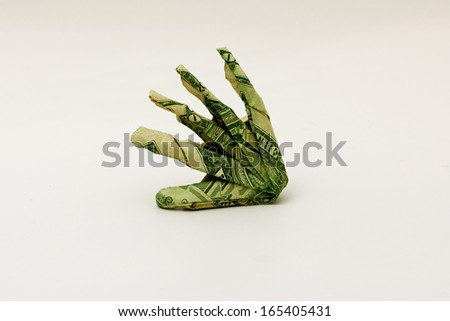 American dollar bills folded into an origami hand - stock photo