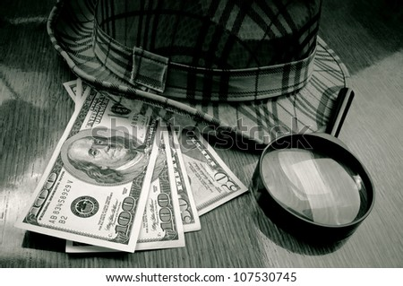 American Dollar-bills, loupe and hat on the wooden table - stock photo