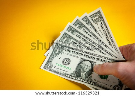 American dollar notes in hand on yellow background - stock photo