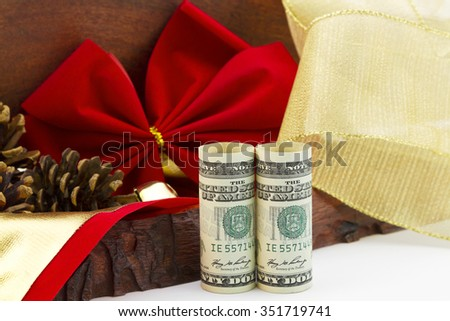 American dollars, a holiday bonus and gift, stand by rustic wooden box, red velvet ribbon, pine cones, and gold ribbon.