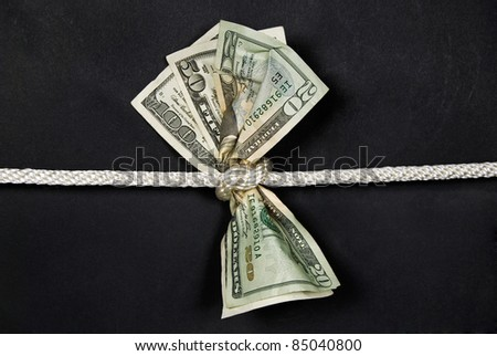 american dollars in a rope knot - stock photo