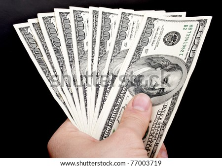 american dollars in hand on a black background - stock photo