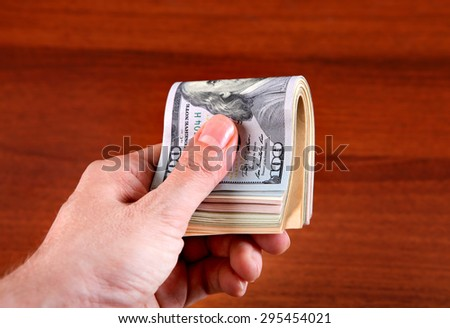 American Dollars in the Hand on the Wooden Table Background